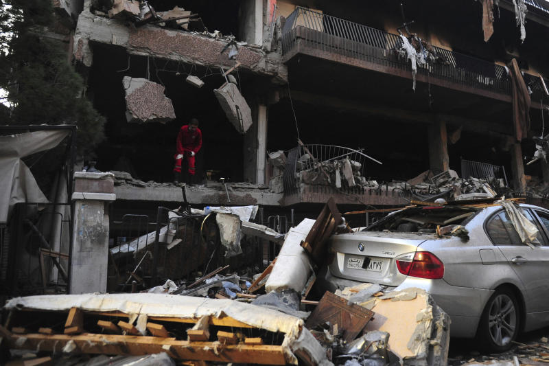 In this photo released by the Syrian official news agency SANA, a Syrian official checks the damage of a building targeted by Israeli missile strikes in the early morning in the Mezzeh area in the capital Damascus, Syria, Tuesday, Nov. 12, 2019. Syria's state-run news agency says Israel has struck a residential building in Damascus housing a commander of the Palestinian Islamic Jihad group with two missiles, killing two people. (SANA via AP)