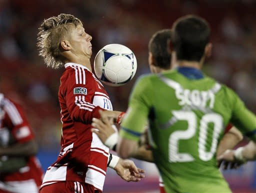 FC Dallas' Brek Shea controls a pass as Seattle Sounders' Zach Scott (20) watches in the second half of an MLS soccer game Wednesday, May 9, 2012, in Frisco, Texas. The Sounders won 2-0. (AP Photo/Tony Gutierrez