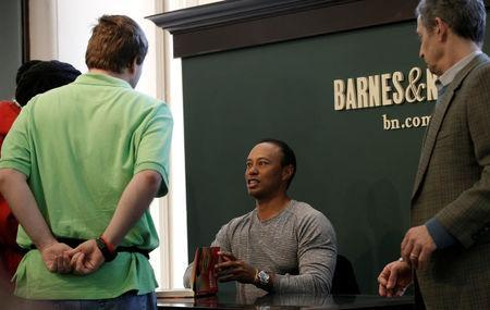 """Golfer Tiger Woods signs copies of his new book """"The 1997 Masters: My Story"""" at a book signing event at a Barnes & Noble store in New York City, New York, U.S., March 20, 2017. REUTERS/Mike Segar"""