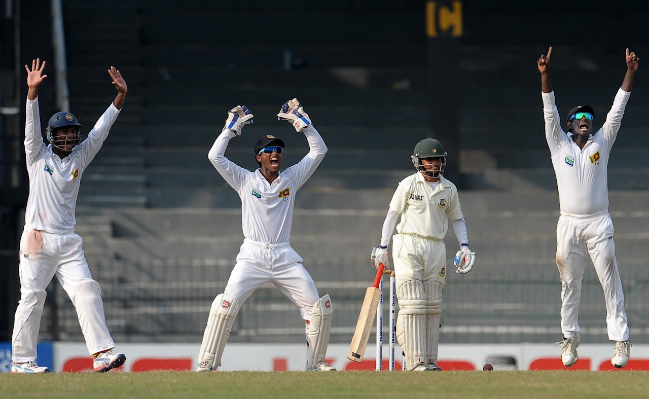 Sri Lankan wicketkeeper Dinesh Chandimal (2L) and Dimuth Karunaratne (L), and captain Angelo Mathews (R) react as they unsuccessfully appeal for a Leg Before Wicket (LBW) decision against Bangladeshi cricketer Mominul Haque (2R) during the third day of their second Test match between Sri Lanka and Bangladesh at the R. Premadasa Cricket Stadium in Colombo on March 18, 2013. AFP PHOTO/ LAKRUWAN WANNIARACHCHI