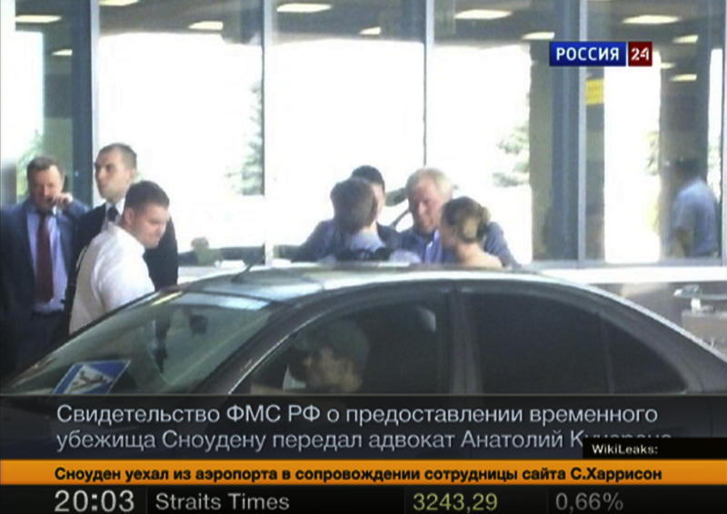 In this still image taken on Thursday, Aug. 1, 2013 and released by Russia24 TV channel, shows Russian lawyer Anatoly Kucherena, second right in the center, and National Security Agency leaker Edward Snowden, center back to a camera, as Snowden leaves Sheremetyevo airport outside Moscow, Russia, on Thursday, Aug. 1, 2013. Snowden has received asylum in Russia for one year and left the transit zone of Moscow's airport, his lawyer said Thursday. Kucherena said that Snowden's whereabouts will be kept secret for security reasons. (AP Photo/Russia24 via Associated Press Television) TV OUT