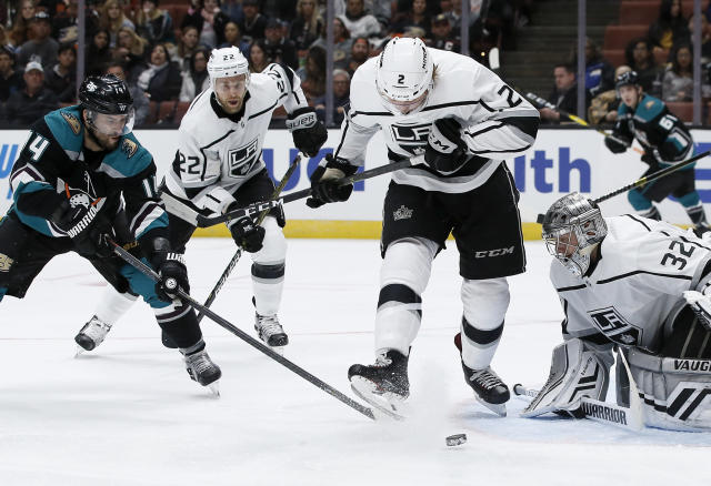 Los Angeles Kings defenseman Paul LaDue, center, kicks the puck away from Anaheim Ducks defenseman Cam Fowler, left, with goaltender Jonathan Quick, right, defending during the second period of an NHL hockey game in Anaheim, Calif., Sunday, March 10, 2019. (AP Photo/Alex Gallardo)