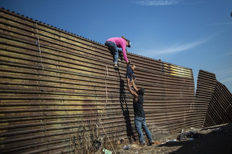 A group of Central American migrants climb the border fence between Mexico and the United States, near El Chaparral border crossing, in Tijuana, Mexico, on Nov. 25, 2018.