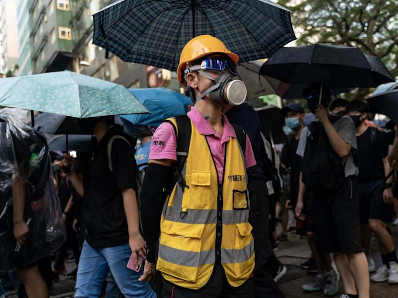 Pro-democracy volunteer stands in front of Tsim Sha Tsui Police Station as protesters march on a street on October 12, 2019 in Hong Kong: Getty