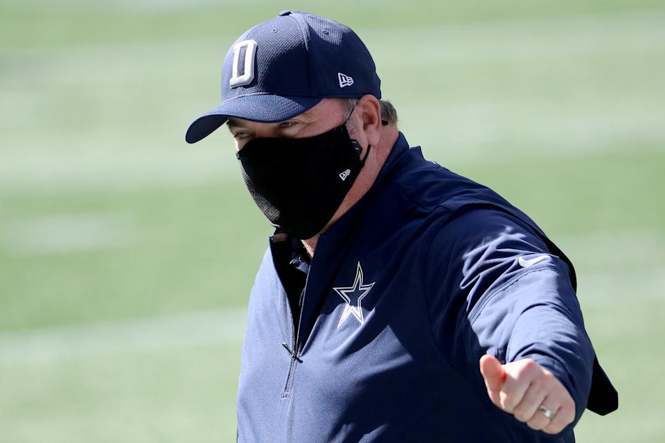 Mike McCarthy wears a face mask and gives a thumbs-up.