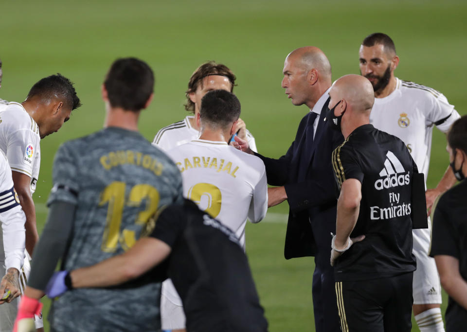 Real Madrid's head coach Zinedine Zidane, third from right, talks with his players during the Spanish La Liga soccer match between Real Madrid and Valencia at Alfredo di Stefano stadium in Madrid, Spain, Thursday, June 18, 2020. (AP Photo/Manu Fernandez)