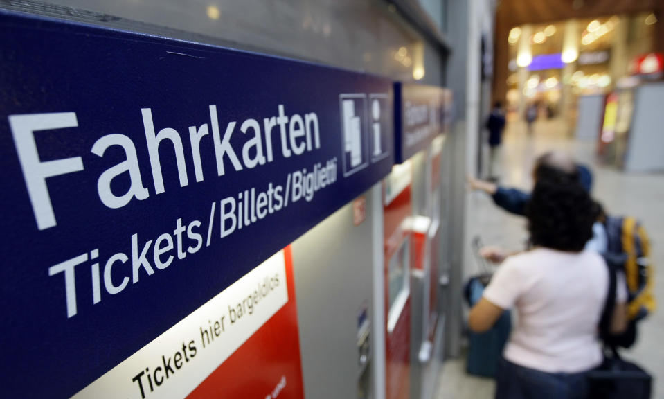 Passenger buy tickets at a ticket machine at Cologne main station September 18, 2008. German rail operator Deutsche Bahn on Friday abandoned plans to introduce a customer service fee for tickets sold at rail stations, a setback for management ahead of the firm's partial privatisation this year.     REUTERS/Alex Grimm