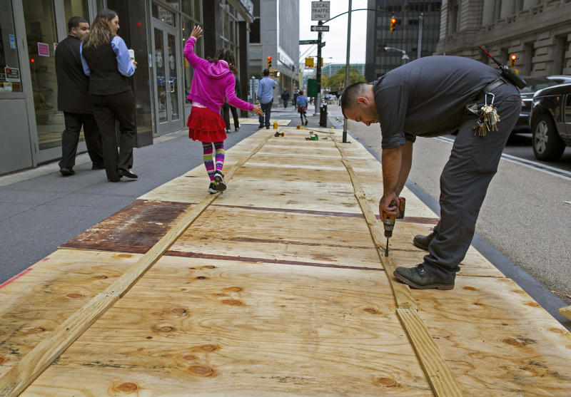 A maintenance worker named Vitto attaches plywood to a sidewalk grate at the 2 Broadway building of Lower Manhattan in New York, Sunday, Oct. 28, 2012, as a child walks along the temporary structure. Areas along the Northeast Coast are preparing for the arrival of Hurricane Sandy and a possible flooding storm surge. (AP Photo/Craig Ruttle)