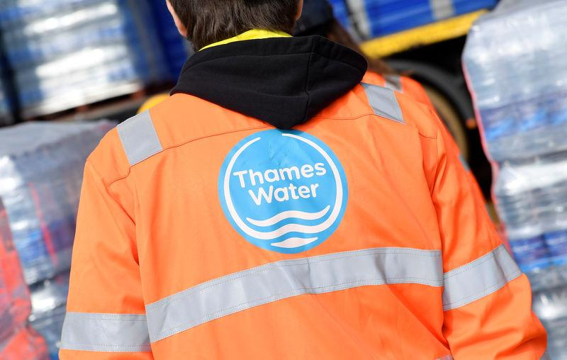 A Thames Water operative views pallets of bottled water for distribution in Hampstead in London, Britain