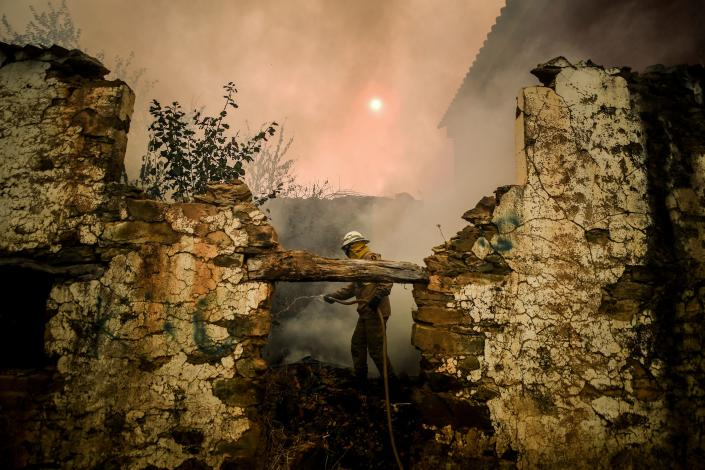 A National Guard Firefighter uses a hose during a wildfire on Roda village in Macao, central Portugal on July 21, 2019. (Photo: Patricia De Melo Moreira/AFP/Getty Images)