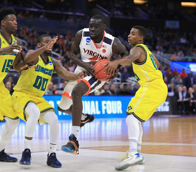 <p>The North Carolina-Wilmington Seahawks try to stop Marial Shayok #4 of the Virginia Cavaliers on his drive to the basket during the first round of the 2017 NCAA Men's Basketball Tournament at Amway Center on March 16, 2017 in Orlando, Florida. (Photo by Mike Ehrmann/Getty Images) </p>