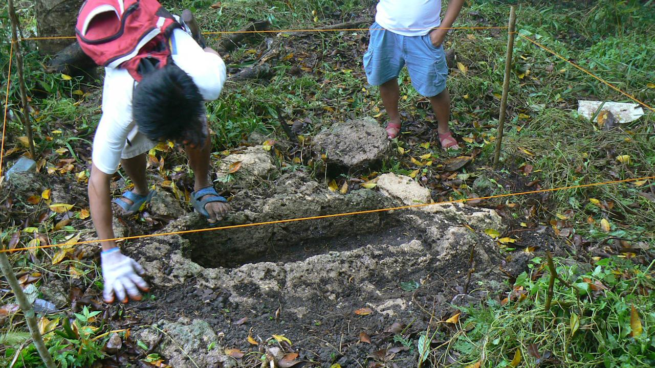 In this March 1, 2011 photo released by the Philippine National Museum, Filipino archeologist clean the area around a limestone coffin at Mount Kamhantik, near Mulanay town in Quezon province, eastern Philippines. Government archeologist have unearthed remnants of what they believe is a 1,000-year-old village on a jungle-covered mountaintop in the Philippines with limestone coffins of a type never before found in this Southeast Asian nation, officials said Thursday, Sept. 20, 2012. (AP Photo/Philippine National Museum) NO SALES, EDITORIAL USE ONLY