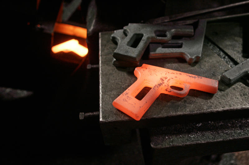 """FILE- In this Dec. 19, 2006, file photo, a molten hot first cut of a model 1911 pistol sits on a shelf between a press and cooling conveyor after being rejected by quality control at the Smith & Wesson factory in Springfield, Mass. Two of the hottest trends in investing are working in tandem to steer billions of dollars toward companies seen as the best corporate citizens. The sustainable investing field in its early days attracted investors by avoiding so-called """"sin stocks""""-- gun makers, cigarette manufacturers, etc. (AP Photo/Charles Krupa, File)"""