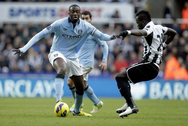 Manchester City midfielder Yaya Toure (L) shields the ball from Newcastle United's Cheick Tiote, on December 15, 2012. Ivory Coast's quarter-final exit at the Africa Cup of Nations means that City manager Roberto Mancini will have both Yaya and Kolo Toure at his disposal for Saturday's visit to Southampton