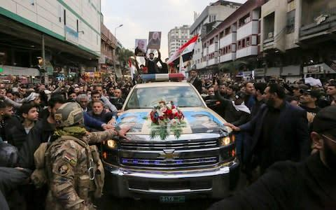 <span>Mourners surround a car carrying the coffin of Iranian military commander Qassim Soleimani</span> <span>Credit: SABAH ARAR/AFP via Getty Images </span>