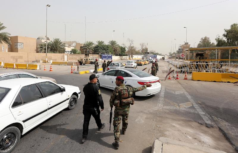"""Members of the Iraqi security force stand guard as cars queue to cross into Baghdad's """"Green Zone"""" on October 5, 2015"""