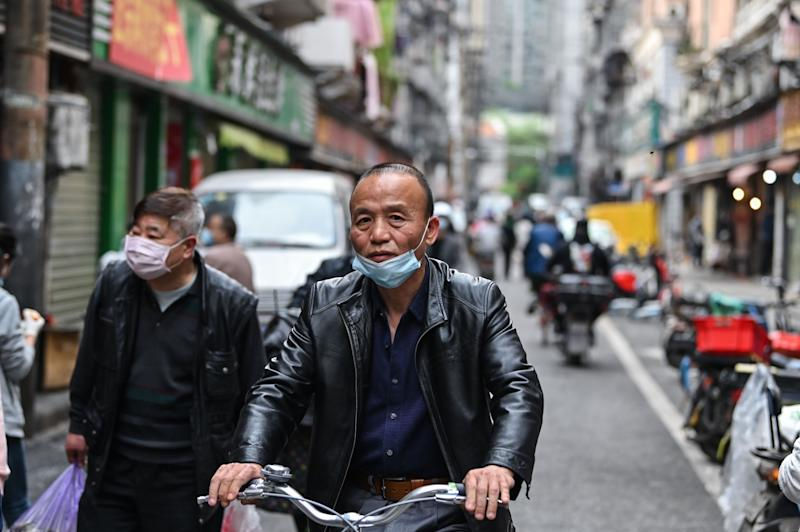 A man wearing a face mask rides a bicycle on a street in Wuhan in China's central Hubei province on April 8, 2020, as travel restrictions to halt the spread of the COVID-19 coronavirus were lifted in the city. - Thousands of Chinese travellers rushed to leave COVID-19 coronavirus-ravaged Wuhan on April 8 as authorities lifted a more than two-month prohibition on outbound travel from the city where the global pandemic first emerged. (Photo by Hector RETAMAL / AFP) (Photo by HECTOR RETAMAL/AFP via Getty Images)