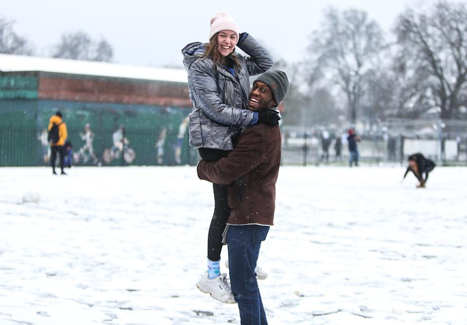 A man carries his girlfriend while playing in the snow on Clapham Common, London, as parts of the UK and Ireland woke up to snow and ice on Sunday morning.