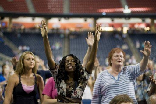 """Members of the crowd pray during the non-denominational prayer and fasting event, entitled """"The Response"""" at Reliant Stadium in Houston, Texas. Texas Governor Rick Perry, expected to launch a 2012 White House bid soon, rallied the faithful for a day of Christian prayer and fasting Saturday asking God to fix America's woes"""