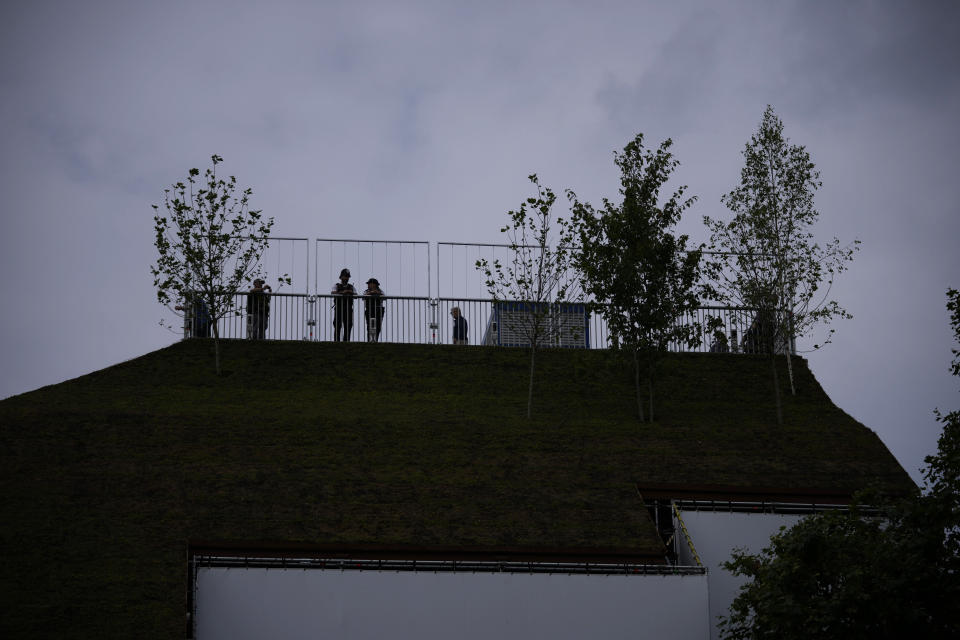 """A police officer and a community support officer are silhouetted as they stand by the viewing area of the newly built """"Marble Arch Mound"""" after it was opened to the public next to Marble Arch in London, Tuesday, July 27, 2021. The temporary installation commissioned by Westminster Council and designed by architects MVRDV has been opened as a visitor attraction to try and entice shoppers back to the adjacent Oxford Street after the coronavirus lockdowns. (AP Photo/Matt Dunham)"""