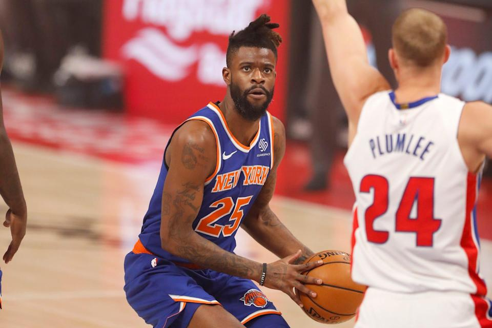 New York Knicks forward Reggie Bullock controls the ball while defended by Detroit Pistons center Mason Plumlee during the first quarter in Feb. 28, 2021, at Little Caesars Arena.