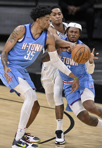 San Antonio Spurs' Devin Vassell, center, pokes the ball from the grasp of Houston Rockets' Ben McLemore, right, as Rockets forward Christian Wood looks on during the first half of an NBA basketball game, Saturday, Jan. 16, 2021, in San Antonio. (AP Photo/Darren Abate)