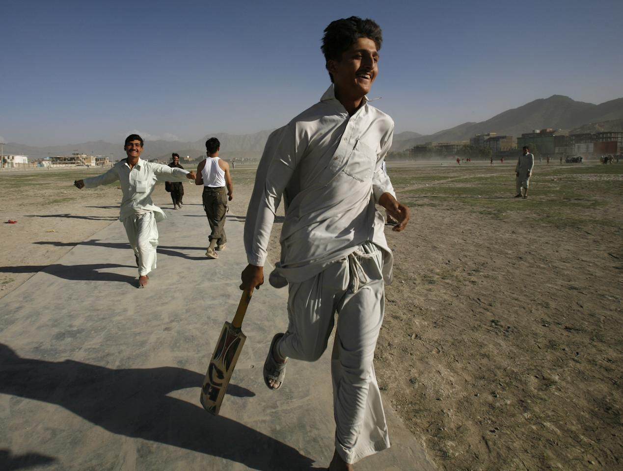 KABUL, AFGHANISTAN - JULY 27:  Afghan cricket players celebrate their team's win during a local league game July 27, 2007 in Kabul, Afghanistan. After the fall of the Taliban when the refugees returned from camps in Pakistan they came back having learned a new sport, Cricket. There are now leagues spread across the country playing in dusty fields. For the average Afghan team the equipment is cheap but the uniforms are not affordable so they play in sandals and their traditional shawal kamis. (Photo by Paula Bronstein/Getty Images)