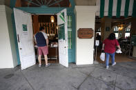 Patrons enter Cafe du Monde Coffee Stand in the French Quarter in New Orleans, Wednesday, Oct. 28, 2020. Businesses that were boarded up for previous hurricanes this season remain open this time as Hurricane Zeta approaches, expected to make landfall as a category 2 hurricane in the afternoon. (AP Photo/Gerald Herbert)