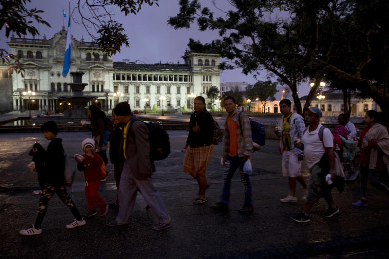 Honduran migrants walk past the National Palace as they leave Guatemala City at sunrise Thursday, Oct. 18, 2018 as they make continue their way north toward the U.S. Many of the more than 2,000 Hondurans in a migrant caravan trying to wend its way to the United States left spontaneously with little more than the clothes on their backs and what they could quickly throw into backpacks. (AP Photo/Moises Castillo)