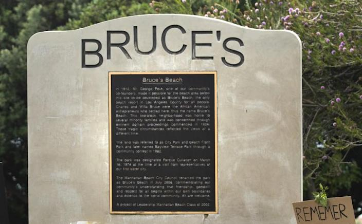 MANHATTAN BEACH, CA -JULY 29, 2020: A commemorative plaque at Bruce's Beach, a park located in Manhattan Beach, explains the history of the area. Bruce's Beach used to be owned by one of the first prominent Black oceanfront homeowners (in the 1920's) but Manhattan Beach ran them out of town and erased/rewrote the history of what happened. A new generation of residents are now calling on the city to confront its racist past. Many have reclaimed the space in recent weeks to celebrate and honor the Black Lives Matter movement. (Mel Melcon / Los Angeles Times)
