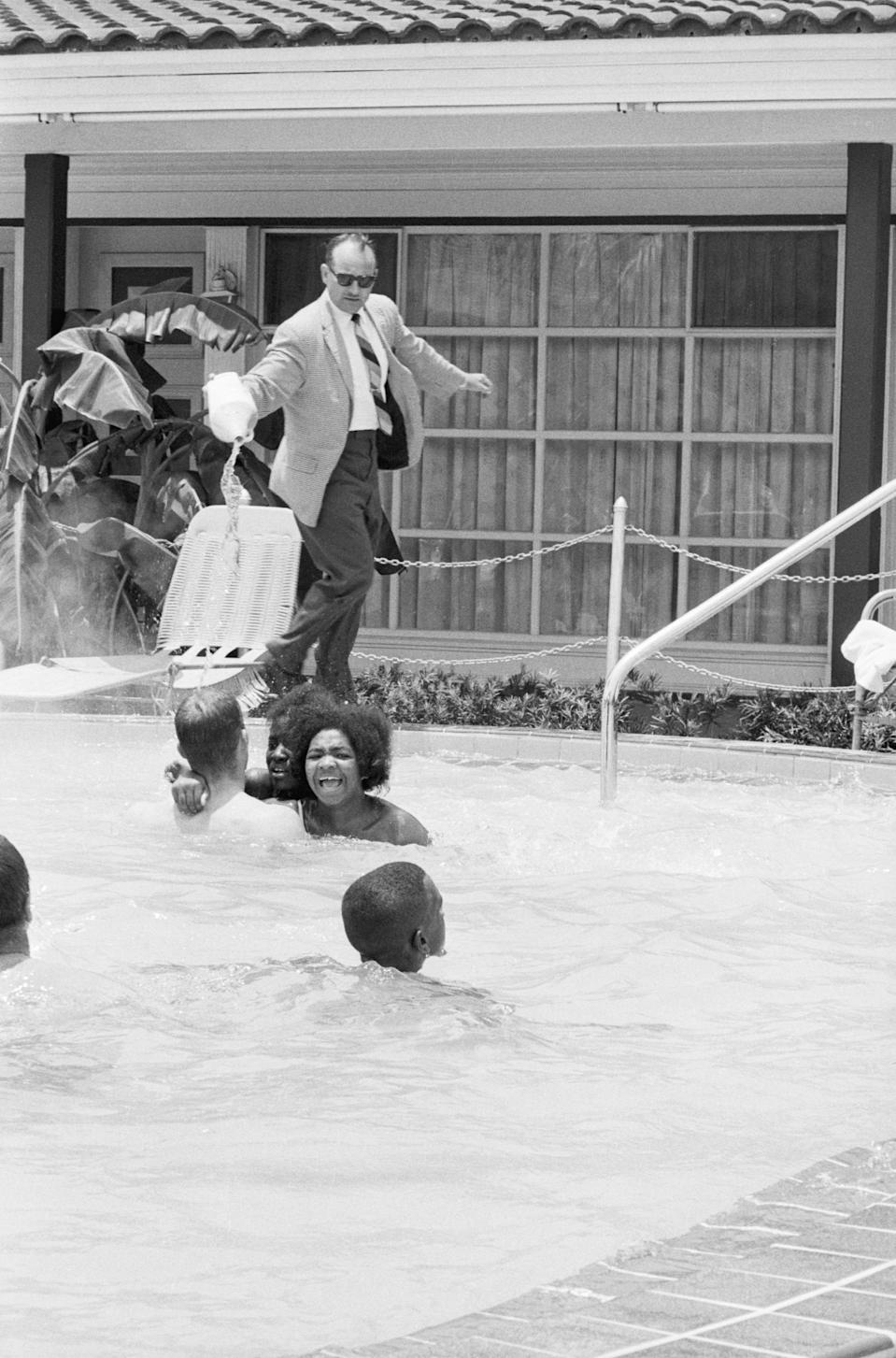 """Protesters demonstrating in the swimming pool of the Monson Motor Lodge in Saint Augustine, Florida scream as motel manager James Brock dumps """"muriatic acid"""" into the water. (AP)"""