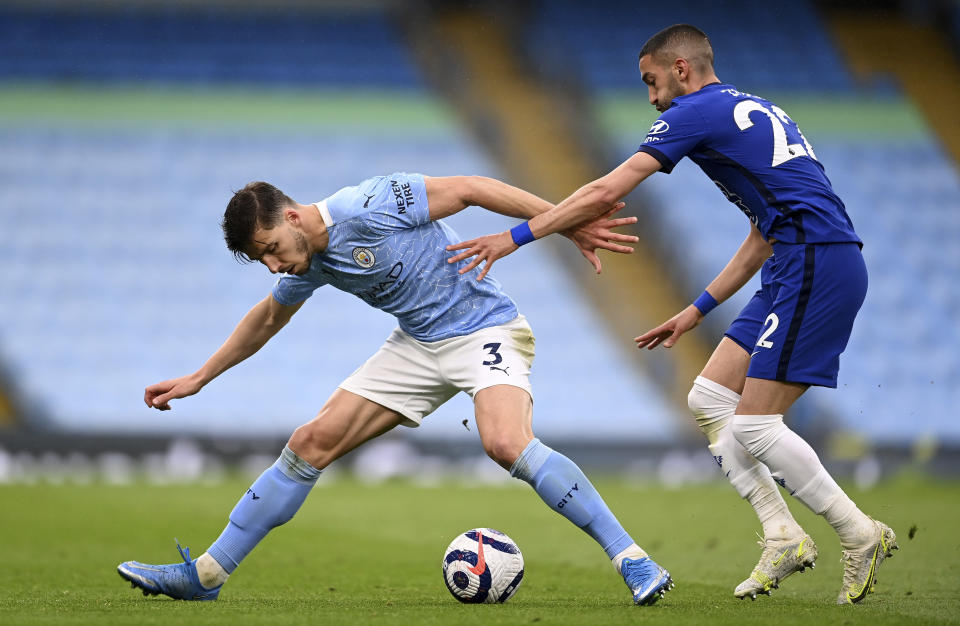 Manchester City's Ruben Dias, left and Chelsea's Hakim Ziyech challenge for the ball during the English Premier League soccer match between Manchester City and Chelsea at the Etihad Stadium in Manchester, Saturday, May 8, 2021.(Laurence Griffiths/Pool via AP)