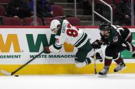 Minnesota Wild left wing Kirill Kaprizov (97) gets tripped by Arizona Coyotes defenseman Niklas Hjalmarsson (4) during the second period of an NHL hockey game Wednesday, April 21, 2021, in Glendale, Ariz. (AP Photo/Ross D. Franklin)