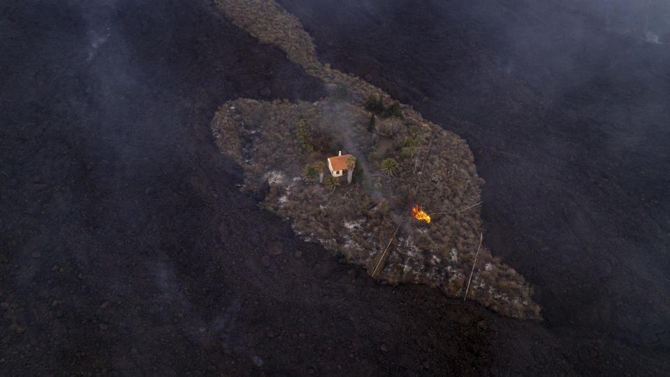 In this photo provided by iLoveTheWorld, a house remains intact as lava flows after a volcano erupted near Las Manchas on the island of La Palma in the Canaries, Spain, Monday, Sept. 20, 2021. A dormant volcano on a small Spanish island in the Atlantic Ocean erupted on Sunday, forcing the evacuation of thousands of people. Huge plumes of black-and-white smoke shot out from a volcanic ridge where scientists had been monitoring the accumulation of molten lava below the surface. (Alfonso Escalero/iLoveTheWorld via AP)
