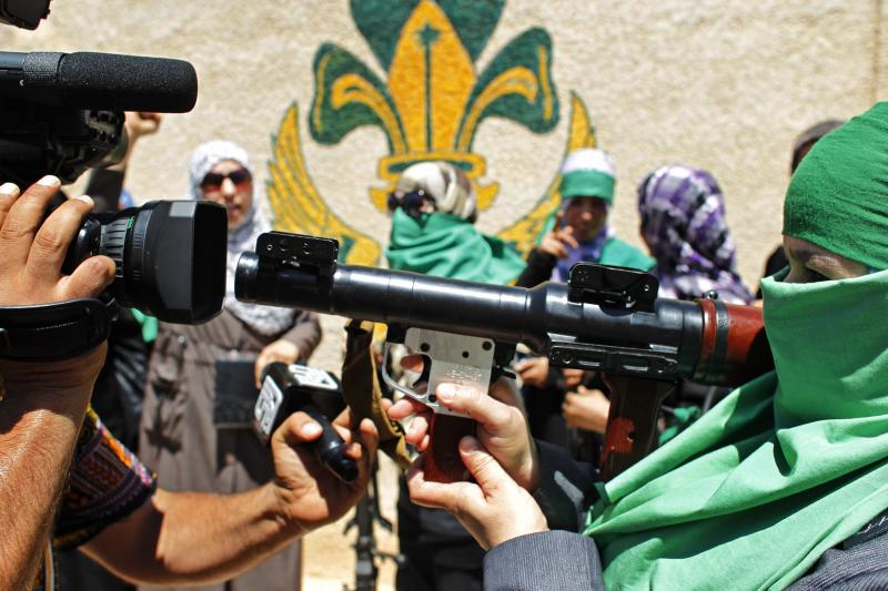 In this photo taken on a government-organized tour, a journalist photographs a Libyan woman as she points her weapon at the video camera in the town of Gharyan, 100 km (62 miles) southwest of Tripoli, Libya, Sunday, July 10, 2011. Moammar Gadhafi's regime is seeking to show it remains in control of parts of the country's western mountains and will defend the territory against further rebel advances there. Journalists based in Gadhafi's stronghold of Tripoli were taken Sunday to the mountain gateway town of al-Gharyan and the nearby town of al-Assabaa. (AP  Photo/Tara Todras-Whitehill)