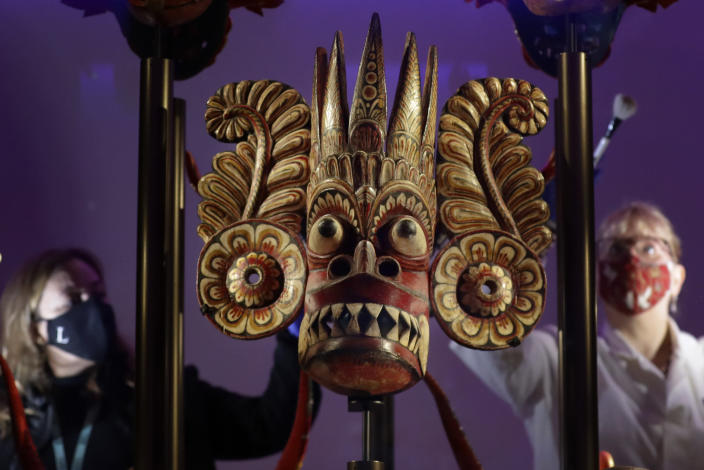 Conservators clean a display of Sri-Lankan masks ranging from 1771-1925, used in healing rituals, displayed in Medicine: The Wellcome Galleries, at the Science Museum in London, Monday, May 17, 2021. The Science Museurm reopens to the public on Wednesday. (AP Photo/Kirsty Wigglesworth)