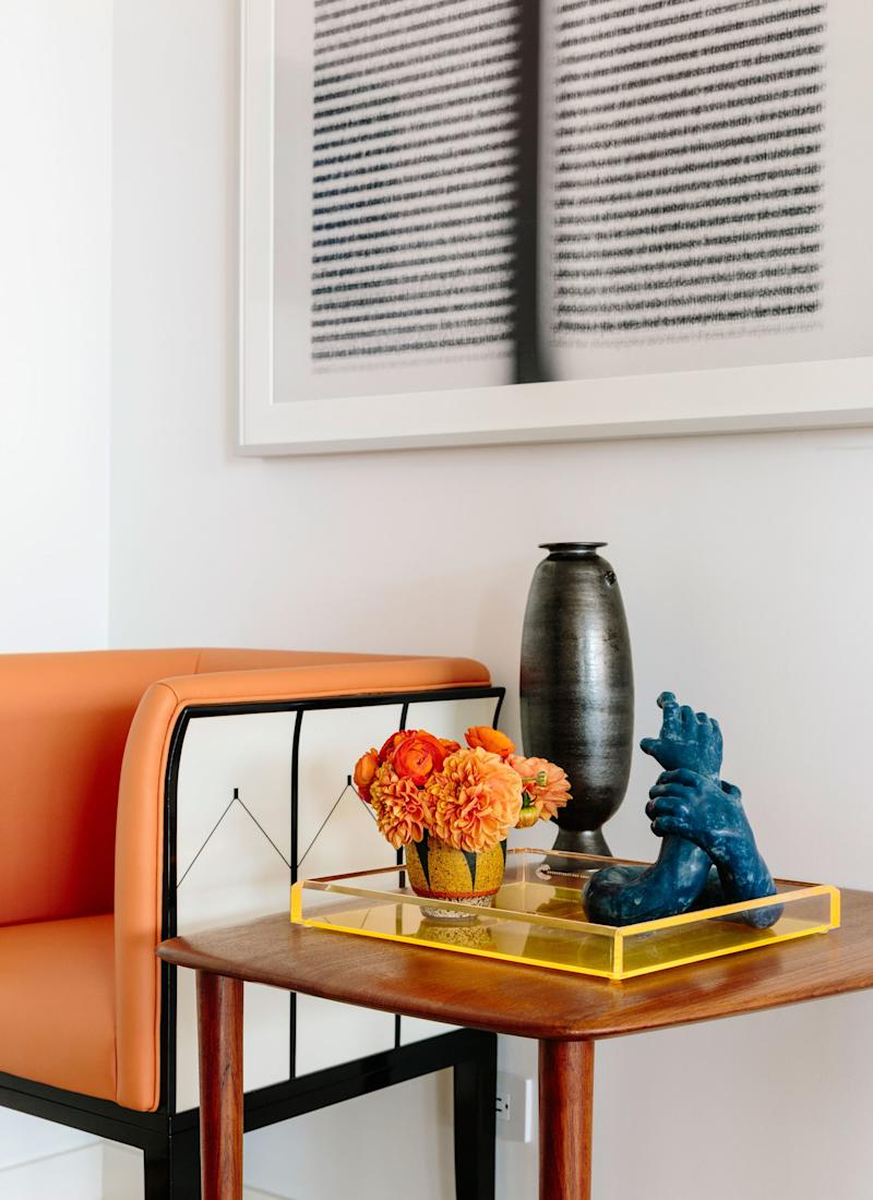 The Eliel Saarinen armchair that Jessica inherited from her grandparents was originally upholstered in a blue fabric, but the couple recovered it in a bold orange one. The framed work is by British artist Idris Khan, who often uses words and texts. Since Sarah is a writer, this piece was a perfect fit for their collection.