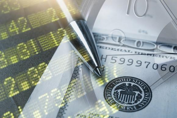 A $100 bill superimposed over a stock index board and a clock.