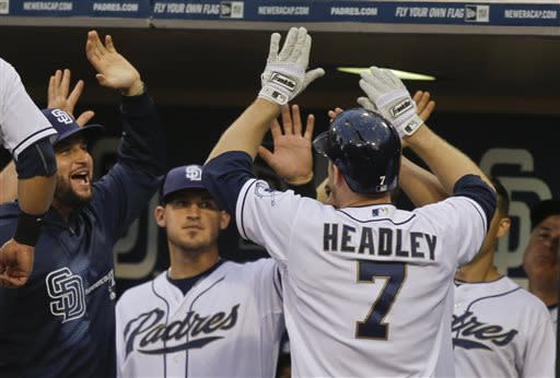 San Diego Padres' Chase Headley is congratulated at the dugout after his solo home run against the Atlanta Braves in the first inning of a baseball game in San Diego, Tuesday, June 11, 2013. (AP Photo/Lenny Ignelzi)