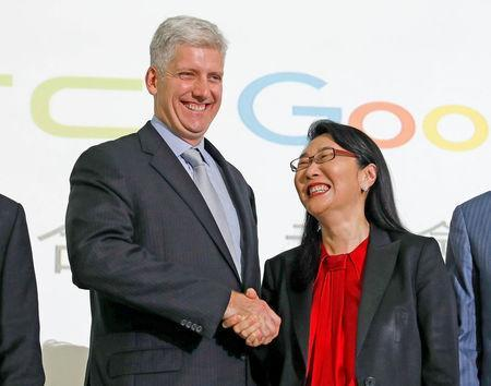 Google hardware executive Rick Osterloh (L) shakes hand with HTC CEO Cher Wang during a news conference to announce Google to acquire HTC's Pixel smartphone division, in Taipei, Taiwan September 21, 2017. REUTERS/Tyrone Siu
