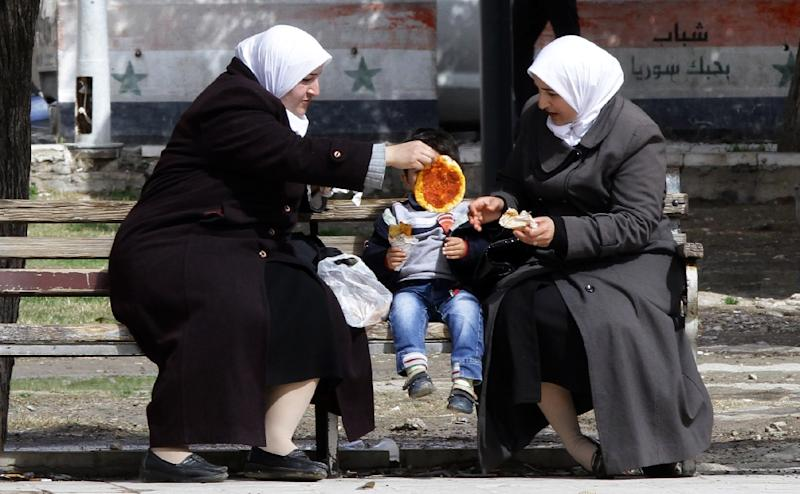 Syrian women sit on a bench as they eat with a young boy in the city of Damascus on March 4, 2015 (AFP Photo/Louai Beshara)
