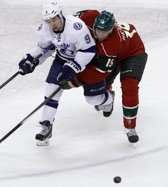 Minnesota Wild left wing Dany Heatley (15), of Germany, tries to keep Tampa Bay Lightning center Tyler Johnson (9) off the puck during the first period of an NHL hockey game in St. Paul, Minn., Tuesday, Feb. 4, 2014. (AP Photo/Ann Heisenfelt)