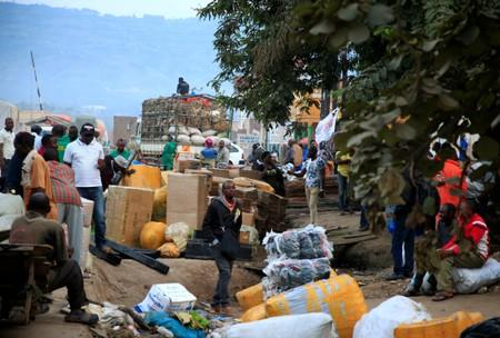FILE PHOTO: Ugandan business people are seen at a market with their merchandises for sale at Mpondwe border that separates Uganda and the Democratic Republic of Congo in Mpondwe