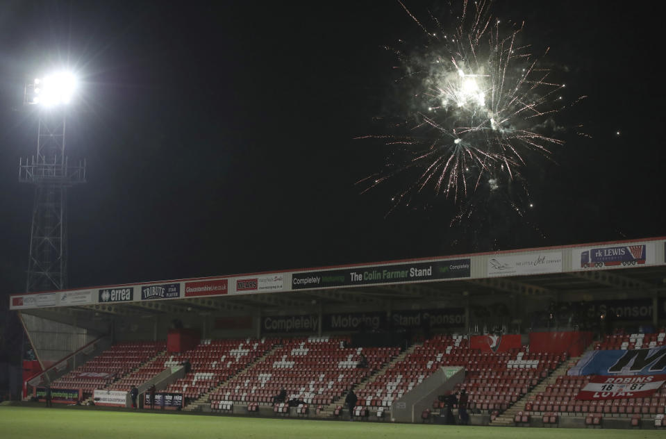 Fireworks explode near the pitch which meant the players were taken off for their safety - resulting in a six minute delay during the English FA Cup fourth round soccer match between Cheltenham Town and Manchester City at the Jonny-Rocks stadium in Cheltenham, England Saturday, Jan. 23, 2021. (Nick Potts /Pool via AP)
