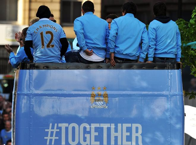 Manchester City players leave on an open-topped bus after becoming English Premier League champions in a parade leaving from Mancheter Town Hall in Manchester, north-west England on May 14, 2012. Manchester City beat their rivals Manchester United on goal difference to be crowned champions on the final day of the season with a 3-2 victory over Queens Park Rangers.     TOPSHOTS/AFP PHOTO/ ANDREW YATESANDREW YATES/AFP/GettyImages