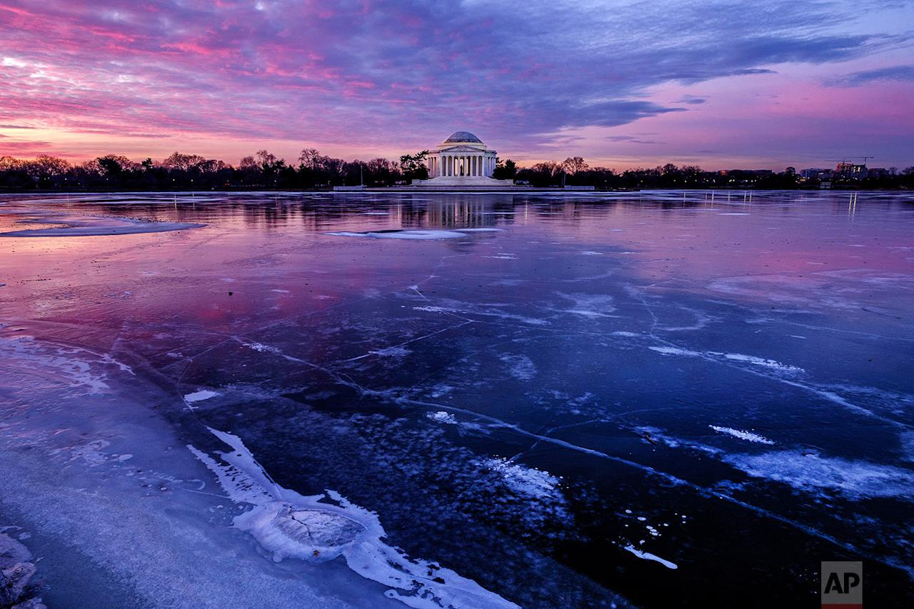 <p>The Jefferson Memorial is reflected in the frozen surface of the Tidal Basin at daybreak in Washington. The Tidal Basin, famous for the Cherry Trees that surround it, is a sheet of ice after several days of bitter cold weather in the Nation's Capital. (AP Photo/J. David Ake) </p>