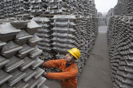An employee checks aluminium ingots for export at Qingdao Port, Shandong province, in this March 14, 2010 file photo. REUTERS/Stringer/Files
