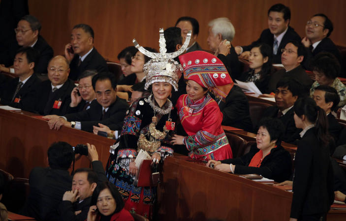 FILE - In this file photo taken Wednesday, March 14, 2012, female delegates in ethnic minority attire take pictures before the closing session of the National People's Congress in Beijing's Great Hall of the People in China. A glance at history suggests it's easier for a Chinese woman to orbit Earth than to land a spot on the highest rung of Chinese politics. In June, the 33-year-old Air Force major marked a major feminist milestone by becoming the first Chinese woman to travel in space. With a once-a-decade leadership transition set to kick off Nov. 8, many now are waiting to see if another ambitious Chinese female, State Councilor Liu Yandong, can win one of the nine spots at the apex of Chinese power. (AP Photo/ Vincent Thian, File)
