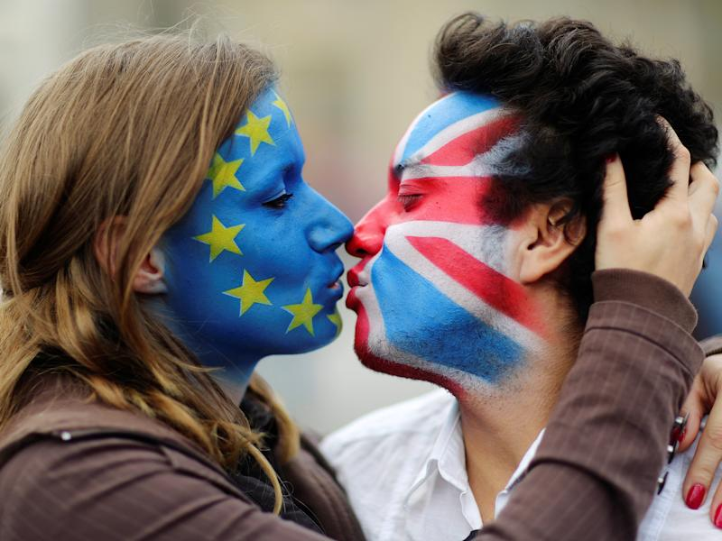 Two activists with the EU flag and Union Jack painted on their faces kiss each other in front of Brandenburg Gate to protest against the British exit from the European Union, in Berlin: REUTERS/Hannibal Hanschke