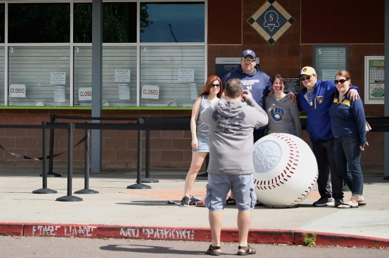 People take photos as closed signs and MLB news releases are displayed on box office windows outside of Peoria Stadium in Peoria, Arizona, where the Seattle Mariners have their Spring Training headquarters